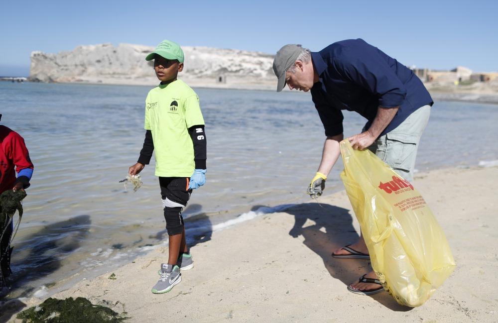 Okeāna krastā vāc izskalotos plastmasas atkritumus.
