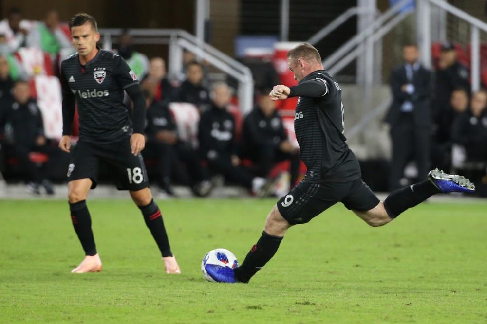 Veins Rūnijs (no labās) izdara tālu un precīzu brīvsitienu MLS čempionāta spēlē.