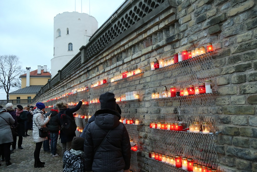 Par godu Lāčplēša dienai, cilvēki noliek svecītes pie Rīgas pils mūra 11.novembra krastmalā.