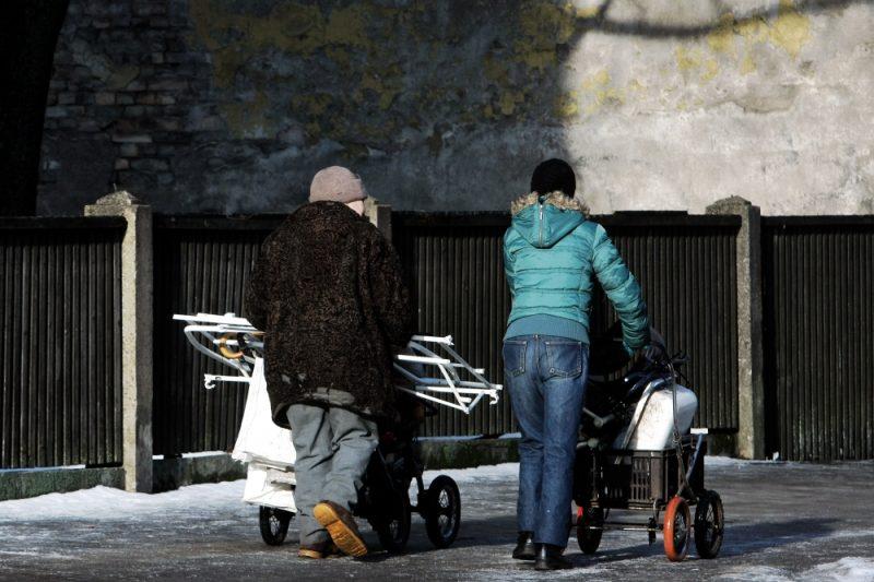 Cilvēki ar ratiņiem ved metāllūžņus.