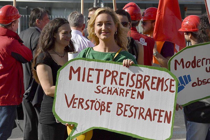"""Sieviete 21. septembrī Valsts kancelejas priekšā Berlīnē piedalās protestā pret augstajām īres cenām ar plakātu """"Pievelciet īres bremzes. Sodiet pārkāpējus!""""."""