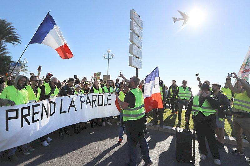 """Protestētāji Nicā 9. decembrī ar plakātu """"Tauta runā"""" iestājas pret degvielas cenu un dzīves dārdzības celšanos. Lēš, ka Francijā """"dzelteno"""" kustībā iesaistījies 31 tūkstotis cilvēku."""
