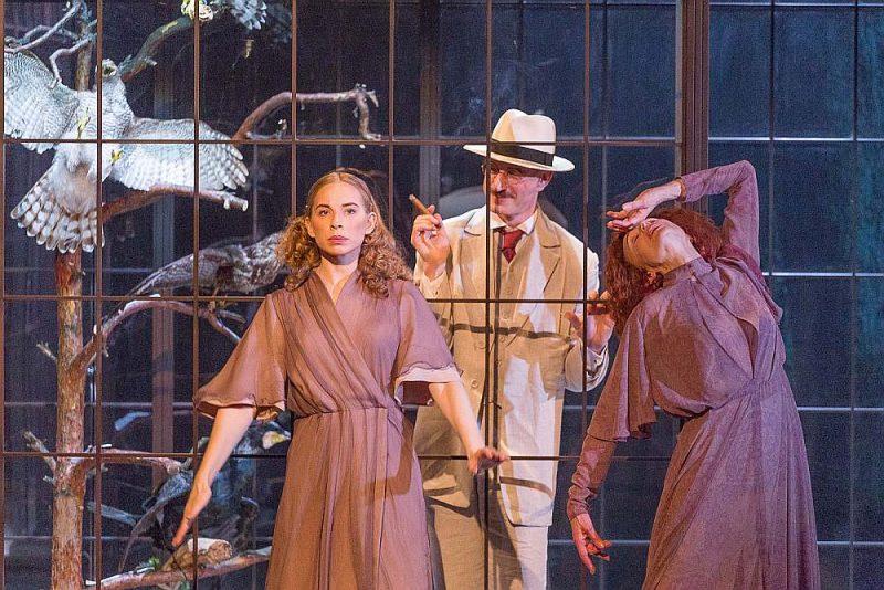 Ulda Tīrona izrādē māte (Regīna Razuma, no labās) un meita (Marija Linarte) padarītas par spoguļattēlu, kas atkārto vienas un tās pašas darbības. Fonā – Ģirta Krūmiņa spēlētais Tomass Manns.