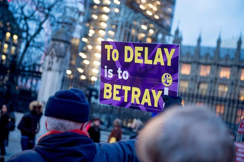 """13. martā pie Apvienotās Karalistes parlamenta ēkas protestēja gan breksita aizstāvji, gan pretinieki. """"Atlikšana ir nodevība,"""" vēsta kāds cietā breksita aizstāvja plakāts."""