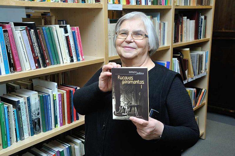 """Latviešu folkloras krātuves pētniece un fondu glabātāja Māra Vīksna rāda izdevumu """"Rucavas garamantas I""""."""