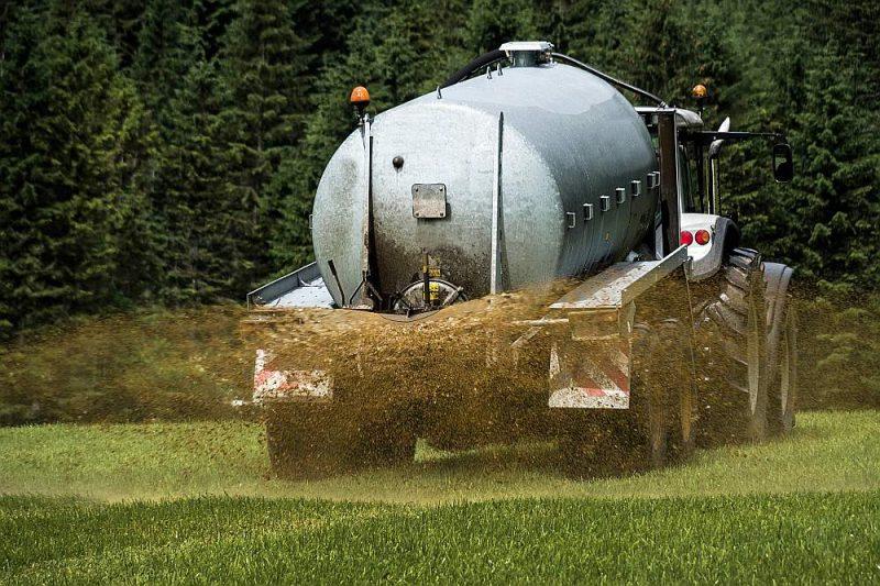 Lauksaimnieks izkliedē šķidros organiskos mēslus uz lauka.