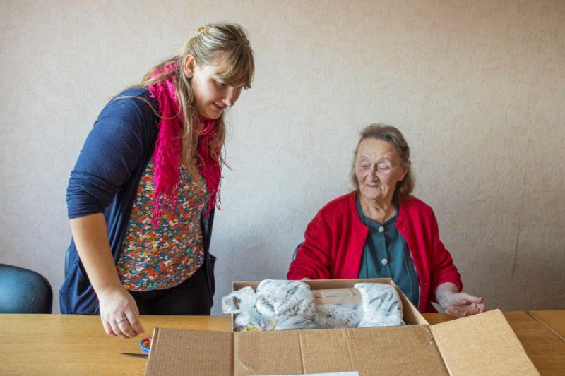 Silvija (no labās) ir priecīga par saticīgajiem līdzcilvēkiem un dāvanu, ko palīdz izsaiņot sociālā darbiniece Anita Ūdriņa.