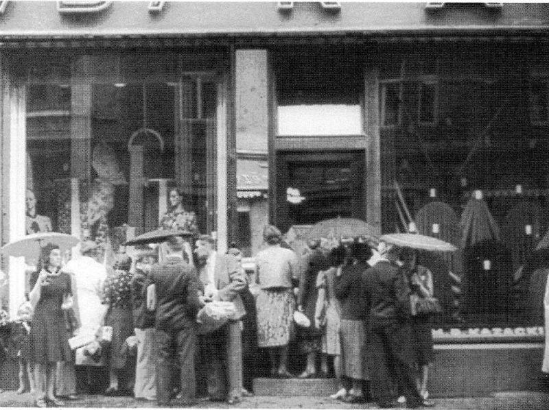 """1940. gada jūlija kinohronikas kadrā ulmaņlaiku Rīgai neierasta rinda pie kāda apģērbu veikala. Tie esot """"tautas ienaidnieki"""" un """"panikas cēlāji"""", toreiz skaidroja padomju varā nonākusī prese."""