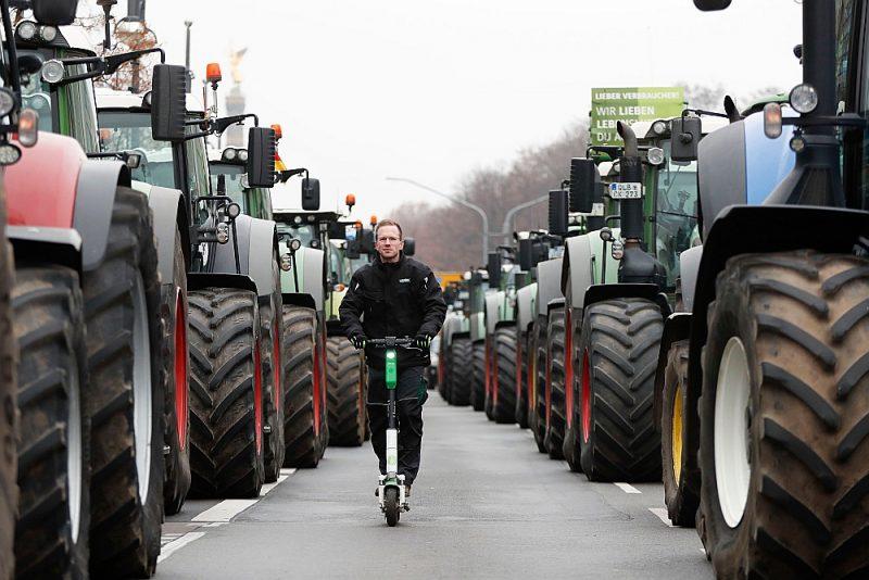 """Latvijas partiju strīda pamatā ir Eiropas Komisijas Zaļā kursa stratēģija """"No lauka līdz galdam"""". Tās viens no mērķiem ir augu aizsardzības līdzekļu jeb pesticīdu samazinājums desmit gadu laikā par 50%. Valdību vēlme samazināt pesticīdu lietošanu sastopas ar pretestību no lielsaimniekiem visā Eiropā. Attēlā: vācu zemnieki pērnruden ar traktoriem devās uz Berlīni, lai protestētu pret plāniem pakāpeniski izbeigt pesticīdu lietošanu, savukārt lauksaimniecības tehnikai pa vidu ar skrejriteni brauc pretējās nometnes – zaļo – pārstāvis."""