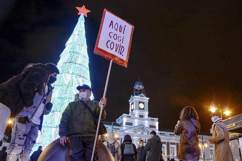 """Madrides pašvaldība uzdevusi policijai novērot un regulēt ieeju pie slavenā Saules vārtu (Puerta del Sol) laukuma. Kāds vīrs 5. decembrī tur stāvēja ar plakātu: """"Šeit es noķēru Covid-19""""."""