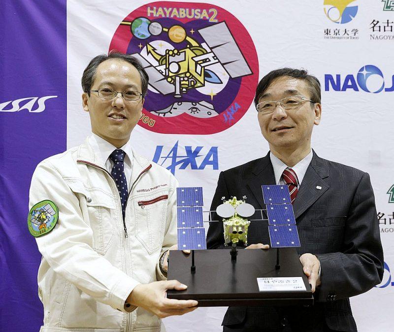 """""""Hayabusa2"""" projekta vadītājs Juiči Tsuda (no kreisās) un  Japānas Kosmosa izpētes aģentūras ģenerāldirektors  Hitoši Kuninaka preses konferencē Tokijā demonstrē zondes """"Hayabusa2"""" modeli."""