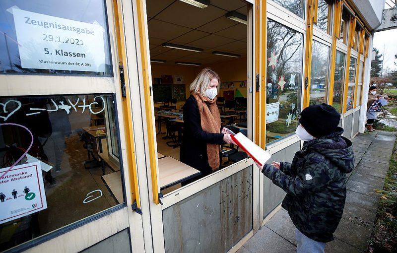 Vācijā skolēni mācās attālināti. Attēlā: janvāra beigās Bonnā skolēns no skolotājas pa klases logu saņem pusgada sertifikātu.