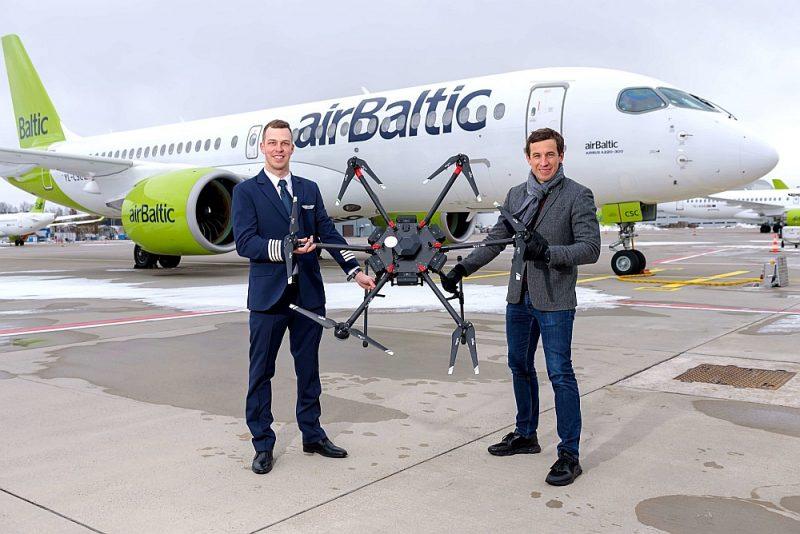 """""""AirBaltic"""" kapteinis Matīss Veiss (no kreisās) un """"LMT"""" viceprezidents Ingmārs Pūķis ir apņēmušies sadarboties, lai attīstītu dronu inovācijas Latvijā."""