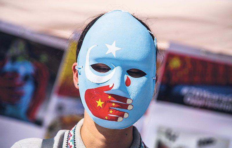 Protestētājs pret uiguru apspiešanu ar uiguru musulmaņu kopienas karoga simbolikas masku, kurai uzlikta roka Ķīnas karoga krāsā. Fotogrāfēts Minhenē, kur izsūtījumā dzīvo ap 800 uiguru.