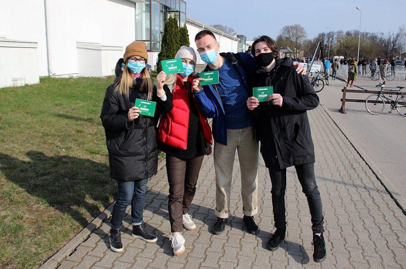 Jaunieši pie vakcinācijas centra Rīgā Ķīpsalas izstāžu hallē rāda apliecinājuma kartītes par saņemto poti pret Covid-19.