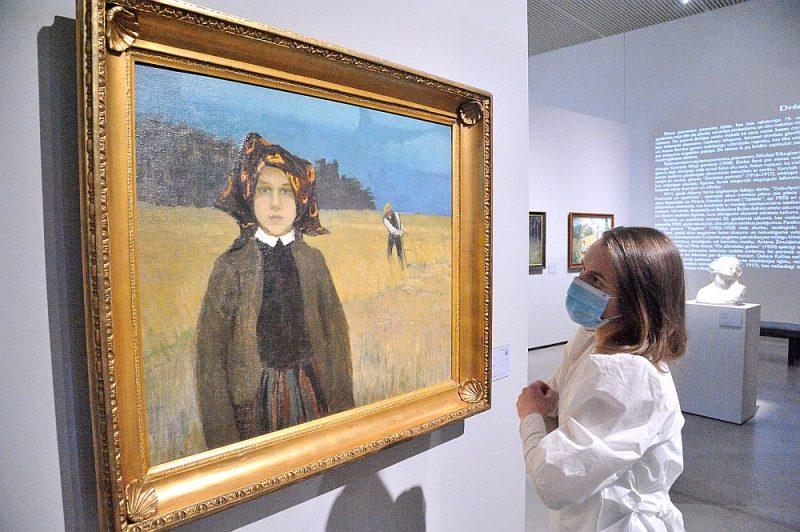 """LNMM Komunikācijas nodaļas vadītāja Annija Sauka pie izstādes """"Nepieradinātās dvēseles. Simbolisms Baltijas valstu mākslā"""" starptautiskās vizītkartes – Johana Valtera gleznas """"Zemnieku meitene""""."""
