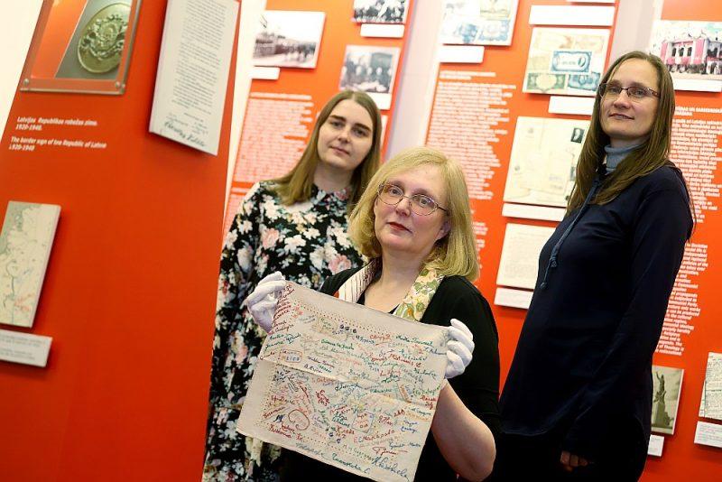 """Okupācijas muzeja pētnieces Evita Freidentāle (no kreisās), Taiga Kokneviča un Lelde Neimane. Taigai Koknevičai rokās ir Mērijas Stakles lakatiņš, kas attēlots arī uz grāmatas """"Mēs tiksimies mūžībā"""" vāka. Ieslodzījumā uz Mērijas baltā kabatlakatiņa tapa uzraksts ar aresta datumu un dažādu tautību likteņa biedreņu paraksti. Mērija vēlāk parakstus izšuva ar krāsainiem diegiem, kas bija ņemti no ieslodzīto drēbēm. Šis izšūtais kabatlakatiņš simboliski atveidots arī uz memoriāla """"Vēstures taktīla"""", kas tagad izveidots Strēlnieku laukumā Rīgā."""