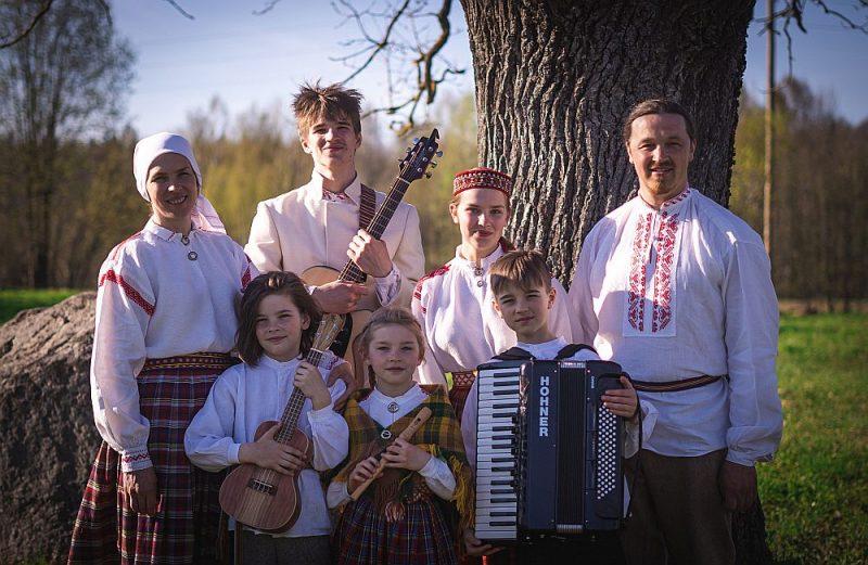 """Folkloras kopā """"Upīte"""" dzied visa tās vadītāja Andra Slišāna (pirmais no labās) ģimene: dzīvesbiedre Ligita Spridzāne (pirmā no kreisās), viņai blakus dēls Domeniks ar ģitāru un vecākā meita Kate. Pirmajā rindā (no kreisās) Miķelis ar ukuleli, Helēna ar stabuli un Jēkabs ar akordeonu."""