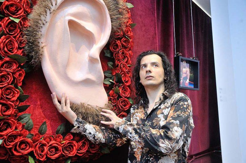 """Multimediju mākslinieka Artūra Bērziņa jaunākās izstādes nosaukums """"Latvijai ausīs jauna diena"""" ir vārdu spēle, kas apspēlē gan ausmas, gan auss kā dzirdes orgāna, gan Lāčplēša mitoloģiskās auss nozīmes. Attēlā mākslinieks pie izstādes darba """"Lāčplēša auss""""."""