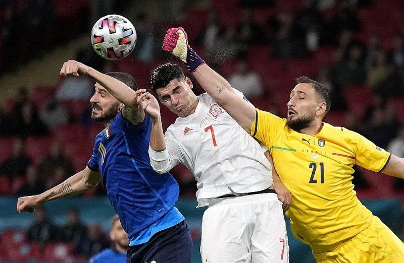 Itālijas izlases vārtsargs Džanluidži Donnarumma (no labās) un aizsargs Leonardo Bonuči neļauj spānim Alvaro Moratam gūt vārtus.