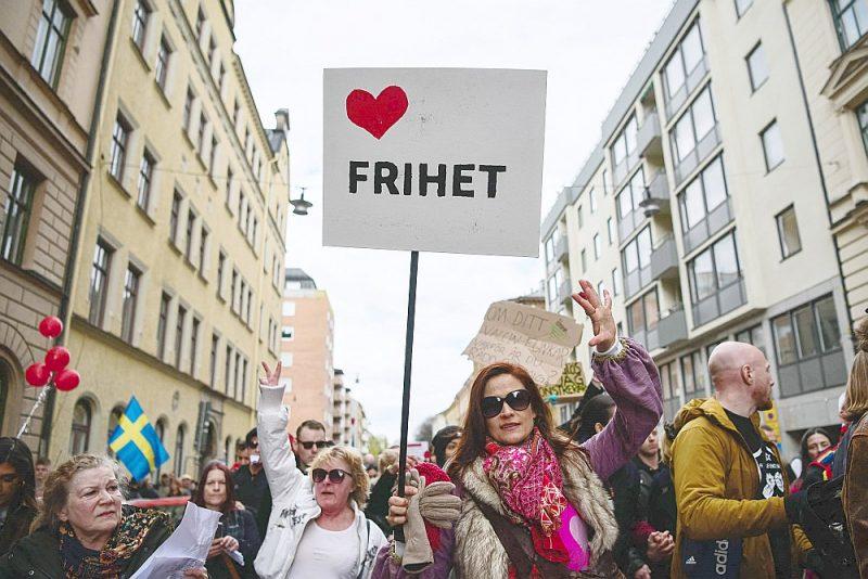 """Zviedrijā pandēmijas laikā bijusi nedaudz citāda pieeja salīdzinājumā ar citām Eiropas valstīm. Taču arī tur ir bijuši ierobežojumi un daļas iedzīvotāju iebildumi pret tiem. Attēlā: protestētāja ar plakātu """"Brīvība"""" mītiņā šā gada maijā."""