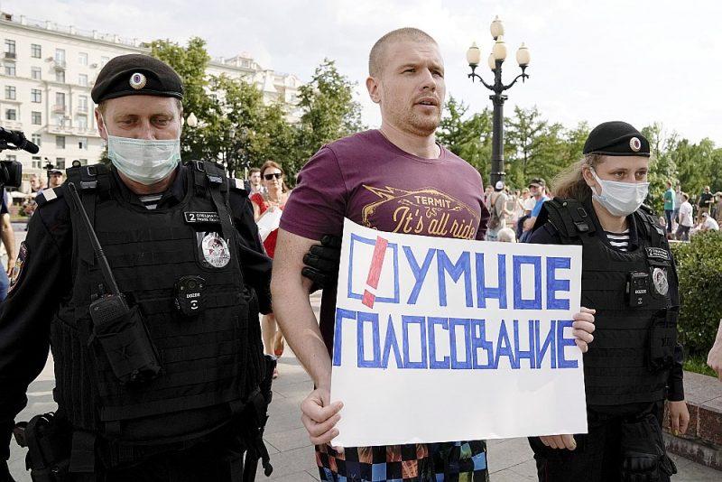 """Krievijas policisti Maskavas centrā aiztur opozīcijas aktīvistu ar plakātu """"Gudrs balsojums""""."""