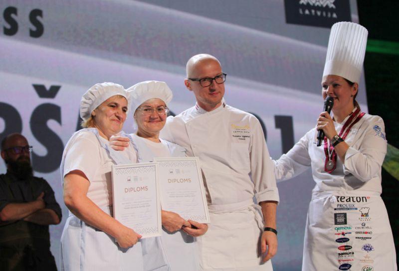 """Pašām par brīnumu, konkursā """"Mana novada garša"""" uzvarēja Rugāju vidusskolas pavāres Valentīna Sproģe (no kreisās) un Iveta Uršuļska. Par panākumu prieks arī viņu mentoram pavāram Romānam Ugļanicam un Pavāru kluba prezidentei Svetlanai Riškovai (no labās)."""